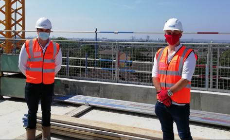 Two men in hard hats on building site